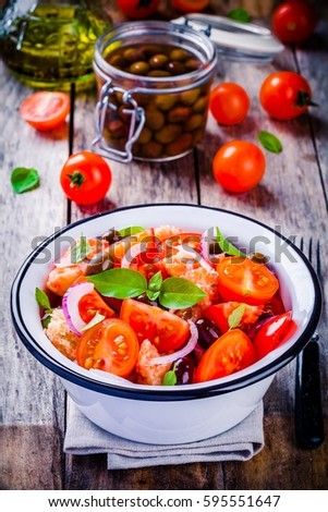 panzanella: Italian salad with tomatoes, ciabatta bread, olives, red onion and basil on a wooden background #595551647