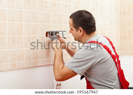 Electrician installing electrical wall fixture - fastening the wires in the receptacle #595567967