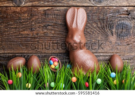 Delicious chocolate Easter bunny and eggs on wooden background Royalty-Free Stock Photo #595581416