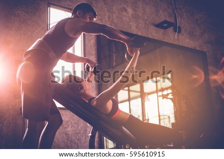 Sporty girl doing weight exercises with assistance of her personal trainer at public gym. Royalty-Free Stock Photo #595610915