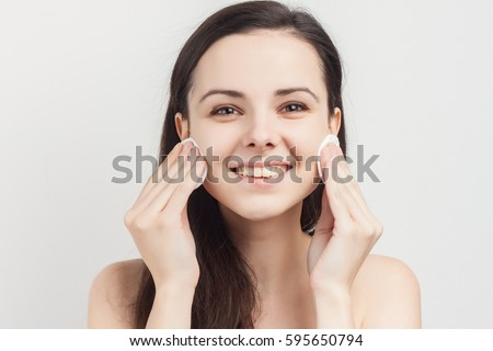 Brunette with a sponge smiling over a light background #595650794