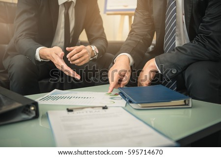 Business people negotiating a contract, they are pointing on a document and discussing together. Two businessmen are negotiating in office. Royalty-Free Stock Photo #595714670