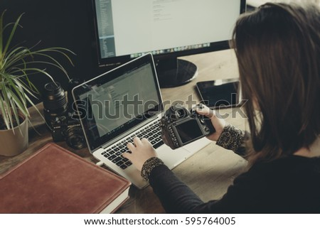 young photographer girl at work in her office, editing pictures on the laptop