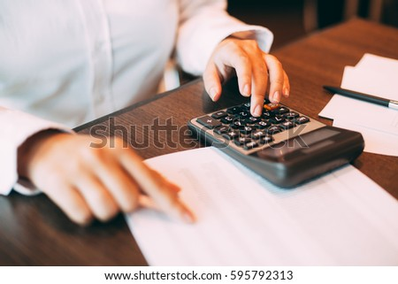 Businesswoman counting with calculator at table #595792313