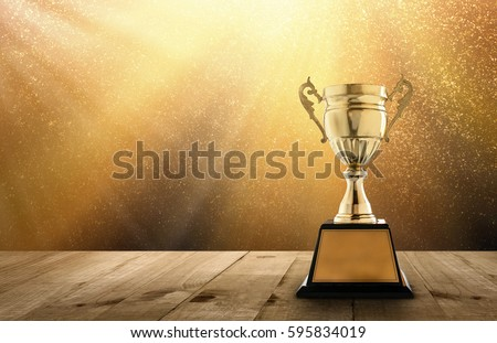 champion golden trophy on wood table with copy space and gold Twinkly Lights and glitter stars light background copy space ready for your design. Royalty-Free Stock Photo #595834019