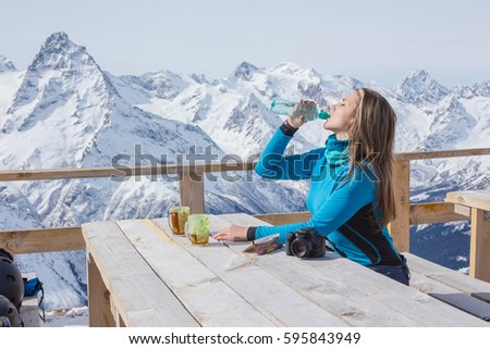 A woman snowboarder drinking water outdoors against a background of snowy peaks. Travel Lifestyle concept active leisure in the open air of winter sports. Sport in the winter mountains. #595843949