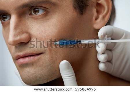 Face Beauty Treatment. Closeup Of Doctor Hands Doing Filler Injections In Handsome Man's Facial Wrinkles. Portrait Of Attractive Young Male Receiving Skin Lift Procedure. Cosmetology. High Resolution #595884995