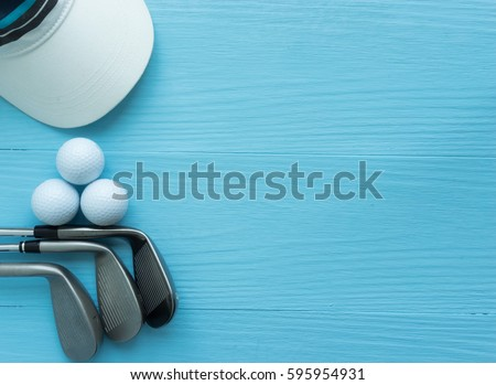 Golf concept : cap, golf balls, golf clubs on wooden table. Top view with copy space.