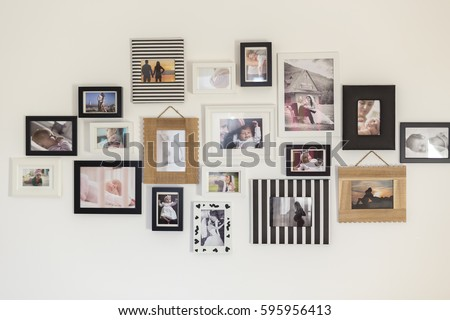 white wall with photos of the family in various photo frames