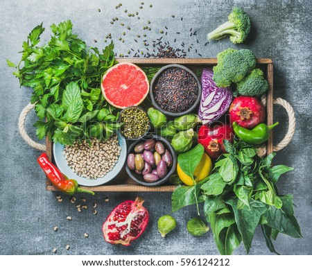 Vegetables, fruit, seeds, cereals, beans, spices, superfoods, herbs, condiment in wooden box for vegan, gluten free, allergy-friendly, clean eating or raw diet. Grey concrete background and top view Royalty-Free Stock Photo #596124212