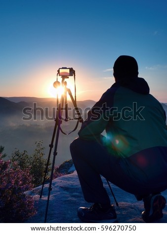 Photographer takes photos with mirror camera and tripod on peak of rock. Fall fogy landscape, spring orange pink misty sunrise in beautiful valley below.