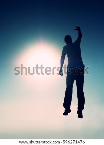 Crazy man is flying over Sun on blue sky background. Silhouette of jumping man and beautiful sunset sky. Element of design. Vintage effect. #596271476