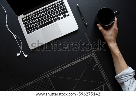 Architectural blueprints on black desk next to laptop and earbuds #596275142