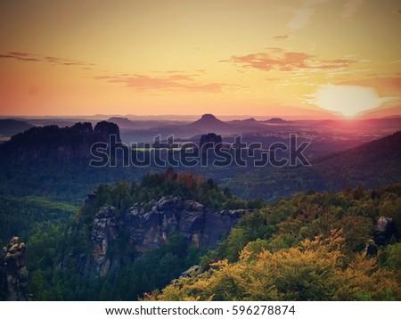 Sunset above sharp sandstone cliffs above deep valley. Popular climbers resort. Deep cracks in rocks donne by strong rain erosion #596278874