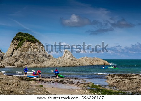 Lee Bay on the north coast of Devon. A group of kayakers are preparing to sail. England Royalty-Free Stock Photo #596328167