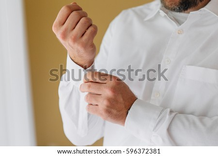 Businessman dressing up for work.Close up portrait of man buttoning his shirt #596372381
