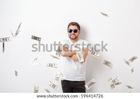 young handsome happy man with a beard in a white shirt standing under money rain of dollar bills #596414726