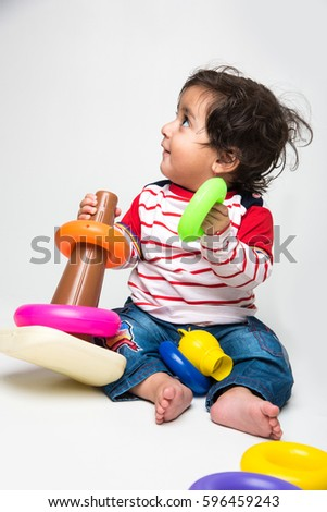 Indian cute little baby /infant or toddler playing with toys or blocks over white background, #596459243