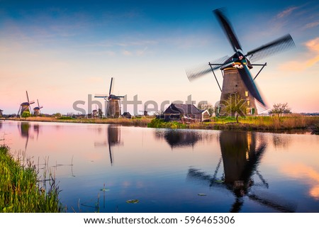 Famous windmills in Kinderdijk museum in Holland, UNESCO World Heritage Site. Colorful spring sunset in countryside. Splendid outdoor scene in Netherlands, Europe. Artistic style post processed photo.