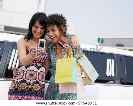 two women standing by limousine and taking picture on mobile phone. Horizontal shape, waist up, copy space