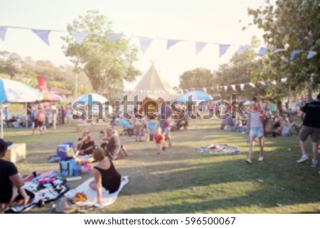 Blur defocused background of people, family in park fair, festive summer, music festival tent Royalty-Free Stock Photo #596500067