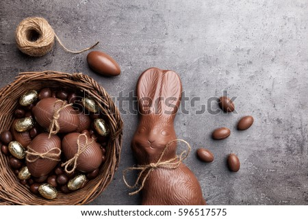 Delicious chocolate Easter bunny and eggs on wooden background Royalty-Free Stock Photo #596517575