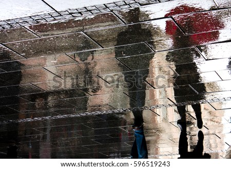 Reflection shadow of a young couple walking in the rain in the city pedestrian zone