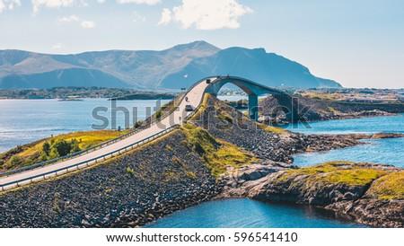 World famous Atlantic road bridge (Atlanterhavsvegen) with an amazing view over the norwegian mountains. Atlantic road runs through an archipelago in Eide and Averøy in Møre og Romsdal, Norway. Royalty-Free Stock Photo #596541410