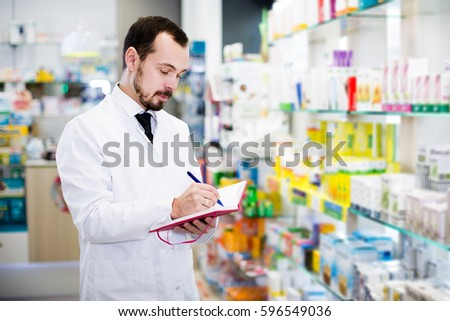 Adult man pharmacist writing down assortment of drugs in pharmacy #596549036