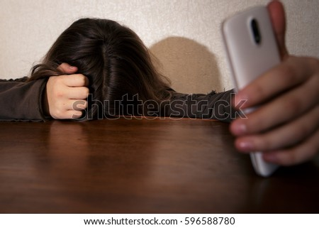 young sad vulnerable teen girl using mobile phone scared and desperate suffering online abuse cyberbullying being stalked and harassed in teenager cyber bullying concept #596588780