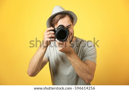 Handsome young photographer on color background Royalty-Free Stock Photo #596614256