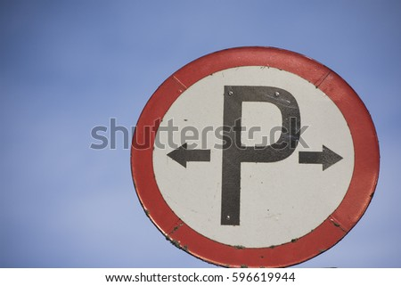Parking here sign red black and white with blue sky background Irish Road Signs