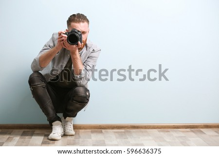 Handsome photographer near color wall
