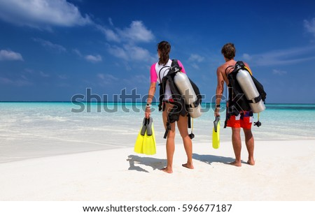 Young couple in scuba diving gear on a tropical beach #596677187
