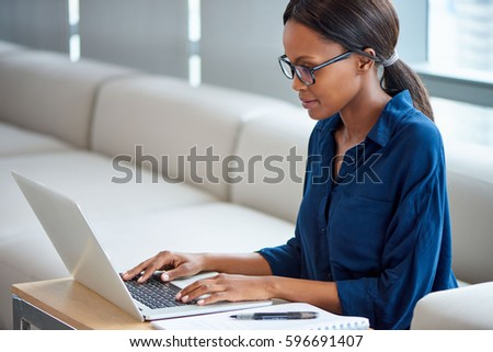Focused young businesswoman wearing glasses working on a laptop while sitting at a table in a modern office #596691407