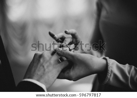 Bride dresses the ring to the groom. Wedding ceremony. Black and white photo #596797817