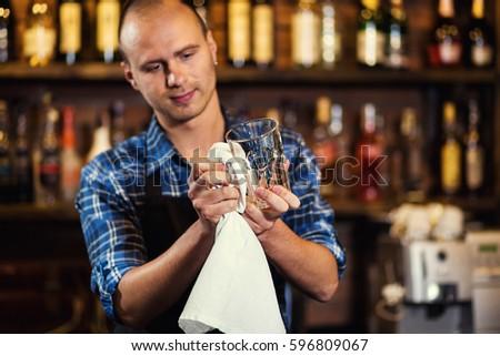 Bartender wipes glasses #596809067
