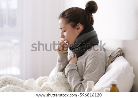 Young ill woman in bed at home Royalty-Free Stock Photo #596816120