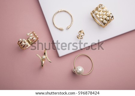 Pearl Golden Bracelets and ring on pink background - Pearl Bracelets on paper background setup  #596878424