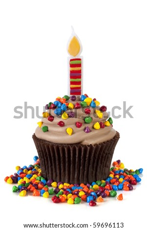 Chocolate cupcake with a fancy candle, topped with colorful sprinkles.  Isolated on white.