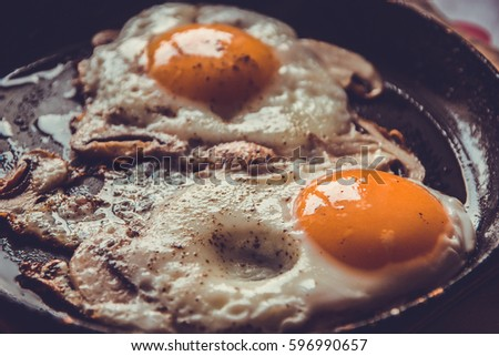 Two fried eggs with mushrooms in a pan. #596990657