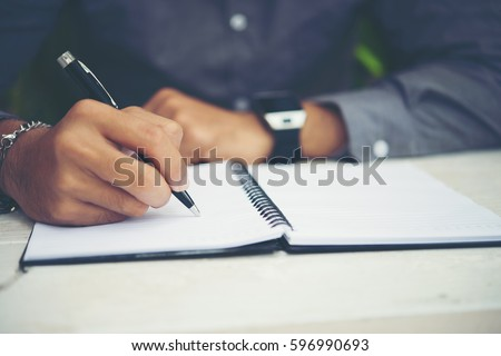Young man hands writing on book in office.Businessman working on desk of wood.Business. #596990693