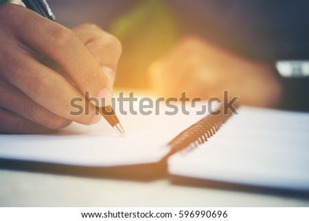 Young man hands writing on book in office.Businessman working on desk of wood.Business. #596990696