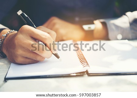 Young man hands writing on book in office.Businessman working on desk of wood.Business. #597003857