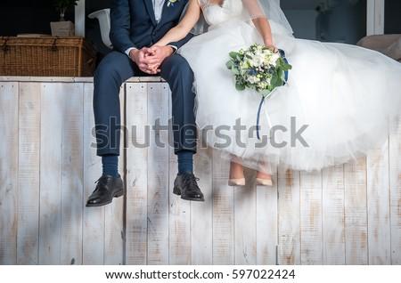 Beautiful wedding couple sitting on wooden pier, swung their legs and enjoying wedding. Royalty-Free Stock Photo #597022424