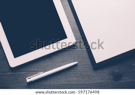 Gadgets and a notebook on a dark wooden background #597176498