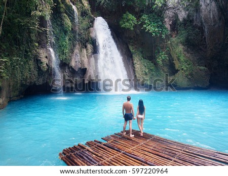 Loving couple by the waterfall #597220964