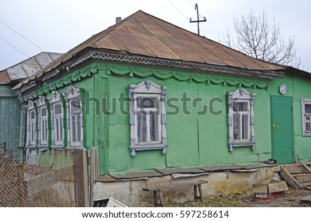 A view of the old house, studded with iron sheets, with beautiful carved wooden windows on the windows and beautiful wooden carvings under the roof in the Russian village. Not far from Tula. Russia #597258614