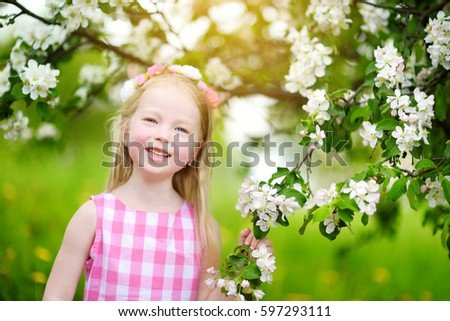 Adorable little girl in blooming apple tree garden on beautiful spring day. Cute child picking fresh apple tree flowers at spring.  #597293111