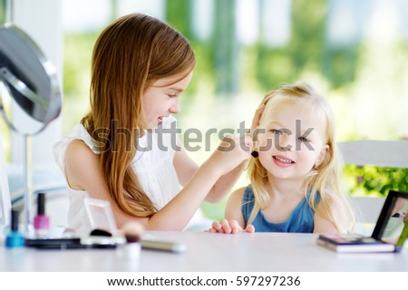 Two cute funny sisters applying make-up on sunny summer day at home. Adorable girls playing with their mommy`s cosmetic accessories.  #597297236